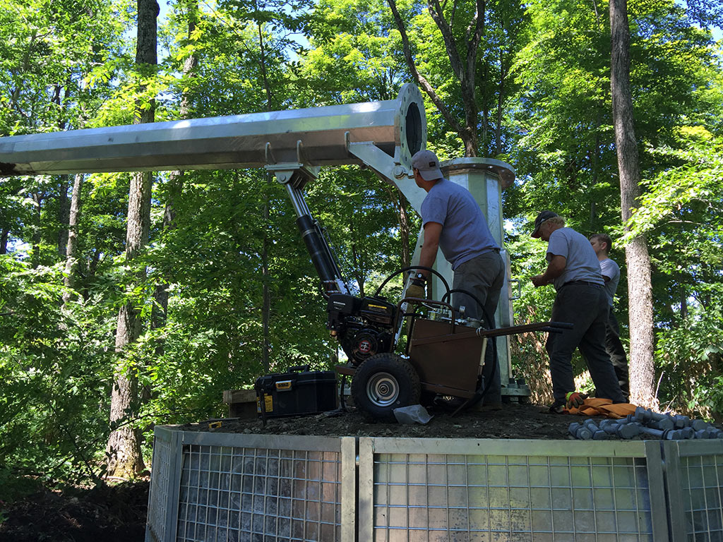 Raising a portable, ballasted monopole tower